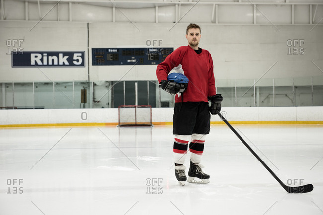 Portrait of male ice hockey player holding helmet and stick at rink