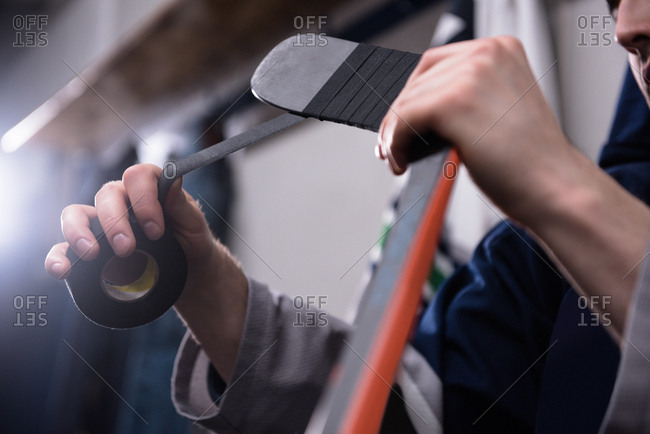 Cropped hands of male player taping ice hockey stick in locker room