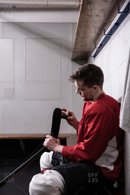 Side view of male player taping ice hockey stick in dressing room