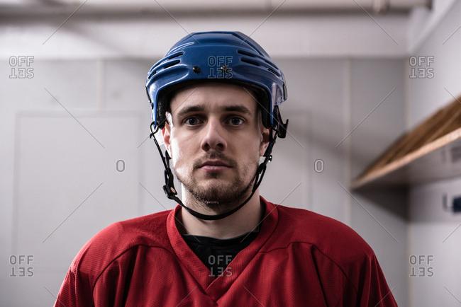 Portrait of male ice hockey player wearing helmet in dressing room