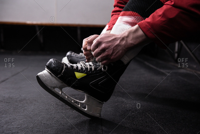 Low section of male hockey player tying ice skate in dressing room