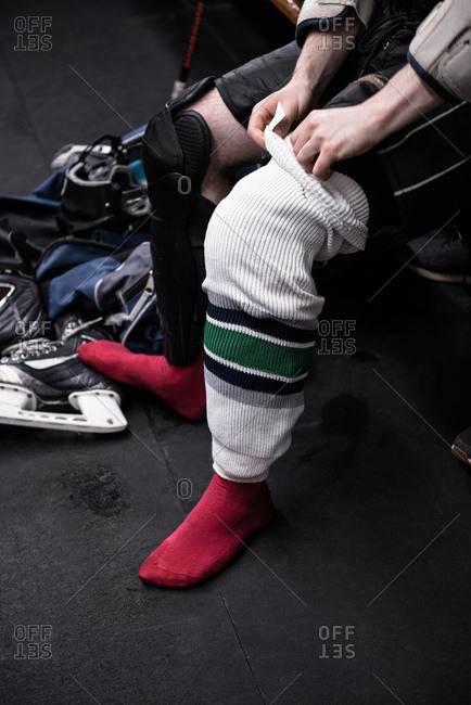 Low section of male ice hockey player wearing sock in dressing room