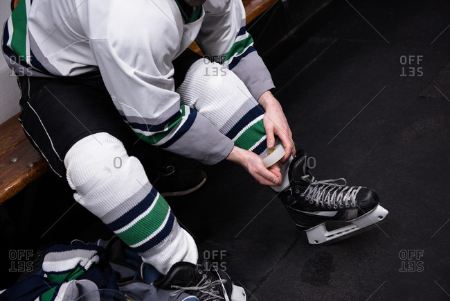 Low section of male ice hockey player wearing skate in dressing room