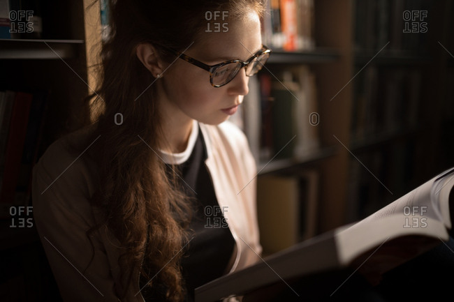 Beautiful woman reading book in library room