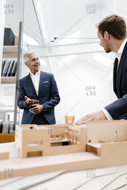 Two businessmen with architectural model in office