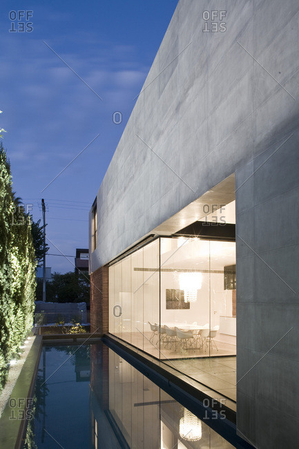 Herzliya, Israel - September 14, 2017: Exterior view of UP House in the evening, grey limestone and glass facade with adjoining swimming pool