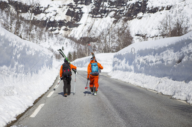 April 17, 2015: Two Skiers Walking On A Road Between Two High Walls Of Snow Near The Ski Resort At Myrkdalen, Fjord, Norway