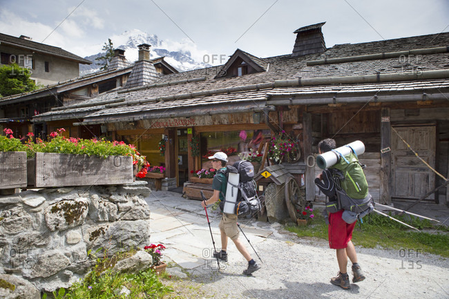 June 25, 2015: Two Hikers With Big Backpacks Enter A Mountain Hostel Near Chamonix, French