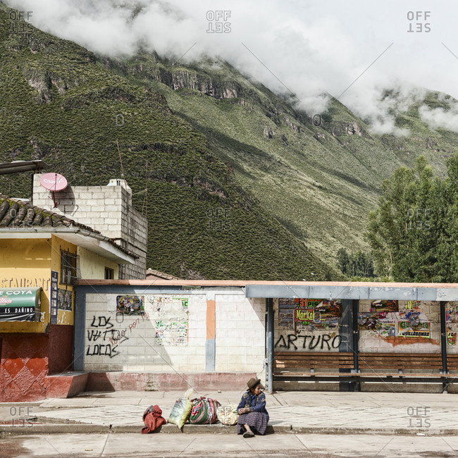 February 27, 2017: A Peruvian Woman Waiting For A Bus With Mountain Rising In The Background