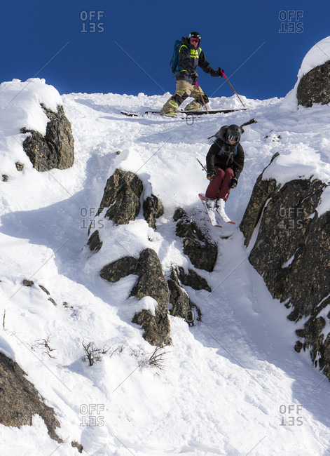 August 3, 2015: A Skier Hits A Small Cliff As His Friend Looks On From Above On A Sunny Day In Bounds At Cerro Cathedral In Patagonia, Argentina.
