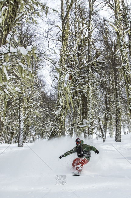 August 16, 2015: Professional Snowboarder Andrew Burns Makes A Turn In The Forest And Sprays Snow In The Air In The Backcountry Around Cerro Cathedral In Argentina