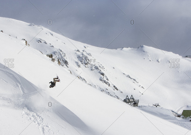 August 17, 2015: A Snowboarder Hits A Wind Lip And Does A Backflip On A Sunny Day In The Backcountry Surrounding Cerro Cathedral In Argentina
