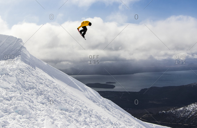 August 17, 2015: A Snowboarder Hits A Backcountry Jump And Does A Tail Grab On A Sunny Day In The Backcountry Around Cerro Cathedral In Argentina