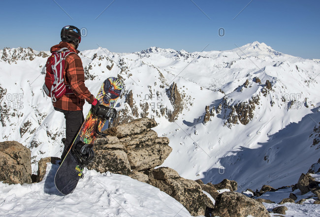 September 4, 2015: A Backcountry Snowboarder Looks Out At The View And Holds His Snowboard After Hiking To The Top Of A Peak Around Cerro Cathedral In Argentina