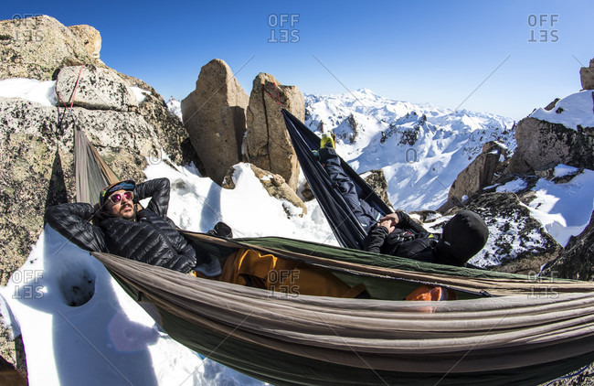 September 2, 2015: Two Men Relaxing In Hammocks At The Top Of The Mountain And Exploring The Andes Around Cerro Cathedral In Argentina