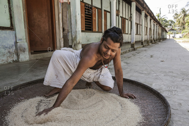 October 24, 2016: A Satra Boy Spreading Rice On Big Hand Woven Tray To Feed Birds, Assam, India