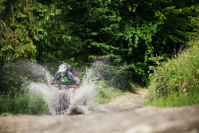 July 13, 2016: A Mountain Biker Bicycling In Water At Forest, Nowy Targ, Poland