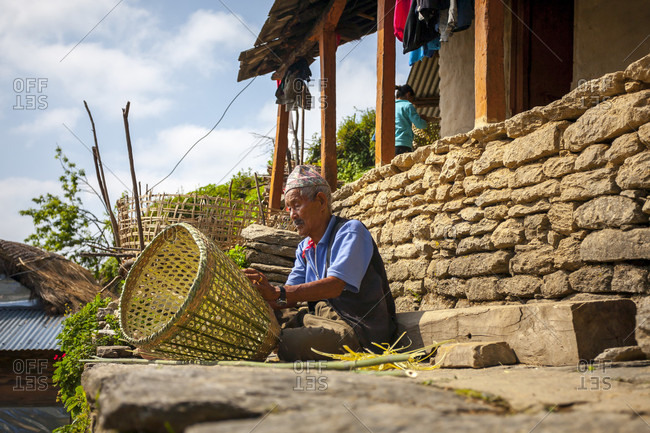 April 3, 2007: An Old Nepalese Man Weaves A Basket Sitting In Front Of His House In A Small Village, Nepal