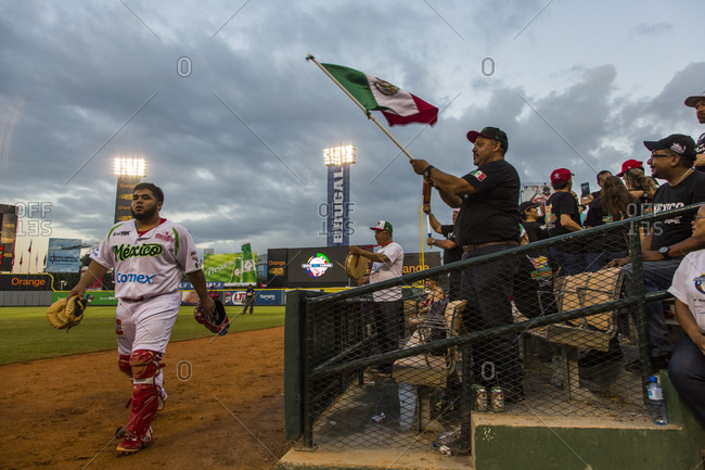 September 12, 2017: A Baseball Player Walks On The Field Next To The Bleachers Where A Man Waves A Mexican Flag In The Dominican Republic