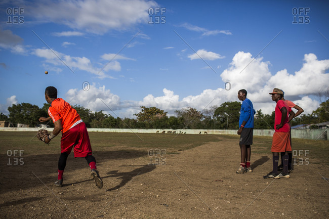 September 12, 2017: Three Young Men Practice Throwing Baseballs On A Sandlot Baseball Field In The Dominican Republic