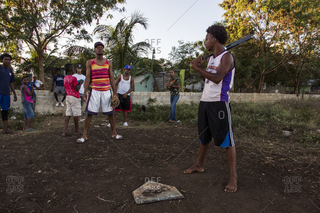 September 12, 2017: Young Men Stand Near A Home Plate On A Sandlot Baseball Field With Kids Standing In The Background Under A Canopy Of Trees In A Rural Village Of The Dominican Republic