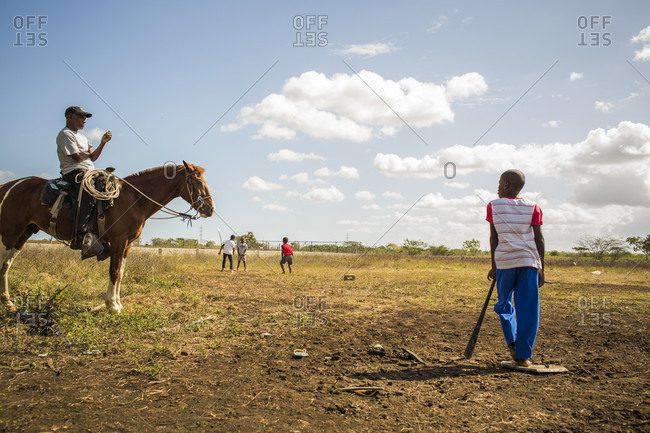 September 12, 2017: A Boy Leans On A Bat At Home Plate On A Rural Sandlot Baseball Field While An Older Man Sits On A Horse In The Dominican Republic
