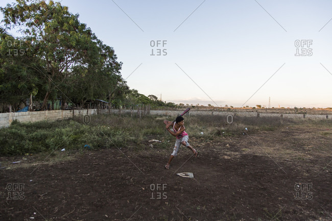 September 12, 2017: A Young Man Swing A Baseball Bat On A Dirt Sandlot At Dusk In The Dominican Republic