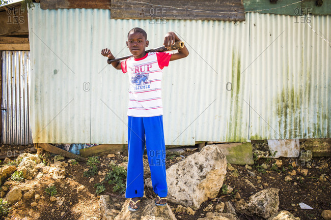 September 12, 2017: A Boy Stands On A Heap Of Rocks Backed By A Metal Shack, Holding A Wooden Bat Over His Shoulders Like A Boss In The Dominican Republic