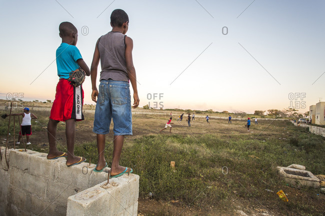September 12, 2017: Two Boys Stand On A Wall Overlooking A Pick-up Baseball Game On A Rural Sandlot Field At Dusk In The Dominican Republic