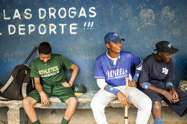 September 12, 2017: Baseball Players Sit On An Old Wooden Bench In A Dugout Against A Blue Painted Wall In The Dominican Republic