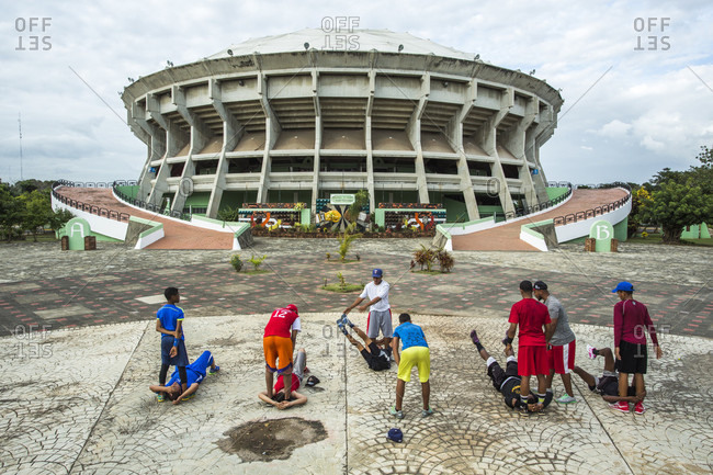 September 12, 2017: A Group Of Teenage Boys Do Training Exercises On A Concrete Lot In Front Of A Large Coliseum In The Dominican Republic