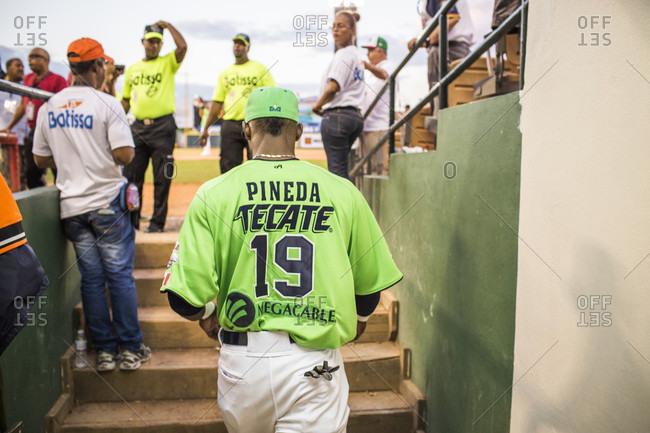 September 12, 2017: A Professional Baseball Player Walks Out Of The Stadium Tunnel And The Security Guards Standing At The Edge Of The Field In The Dominican Republic