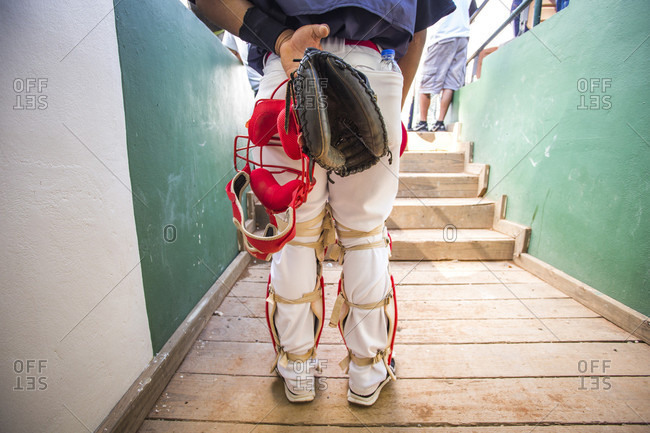 September 12, 2017: Shot From Behind A Baseball Catcher Stands With Mask And Glove Held Behind His Back In A Stadium Tunnel During The Playing Of The National Anthem In The Dominican Republic