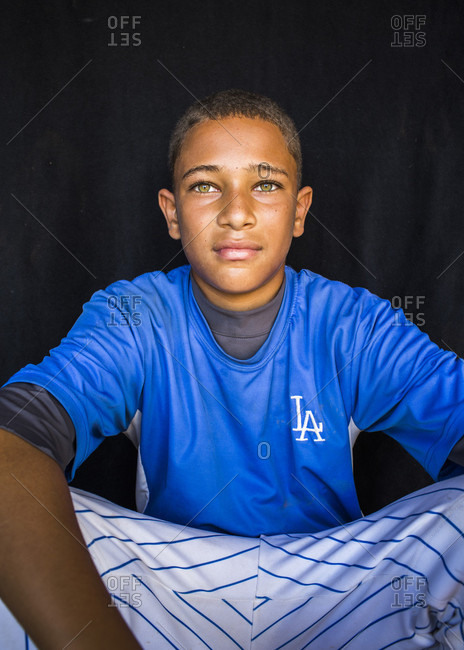 September 12, 2017: A Teenage Boy In Blue Baseball Uniform Sits Against A Black Backdrop And Looks Into The Camera, Santo Domingo, Dominican Republic