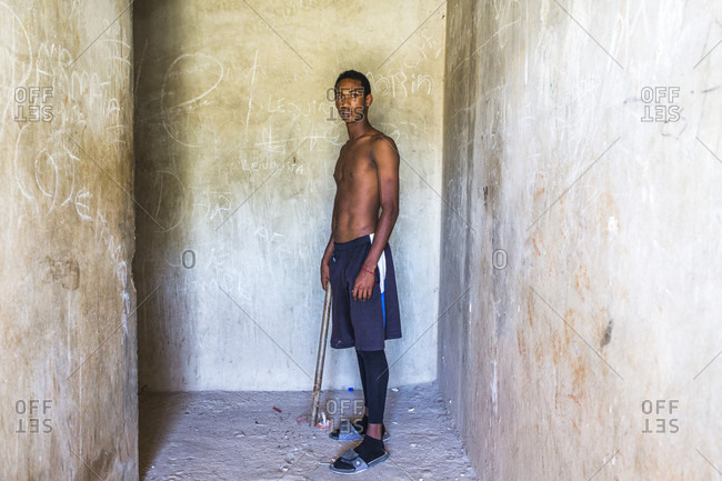 September 12, 2017: A Shirtless Teenage Boy Stands In A Concrete Hallway Holding A Baseball Bat And Looking At The Camera, Santo Domingo, Dominican Republic