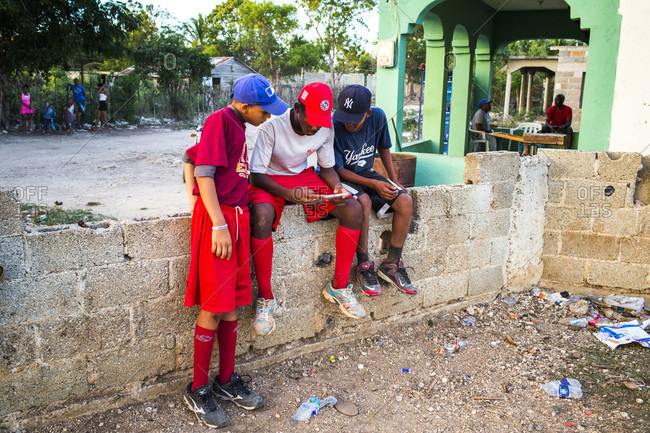 September 12, 2017: Three Boys In Baseball Clothes Look At A Smart Phone While Sitting On A Wall In A Rural Of Latin America