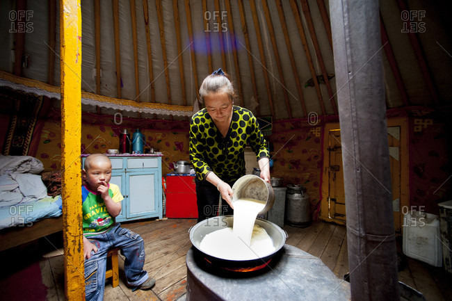 June 2, 2011: Son Looking At Her Mother Cooking The Goat Milk In The Yurt