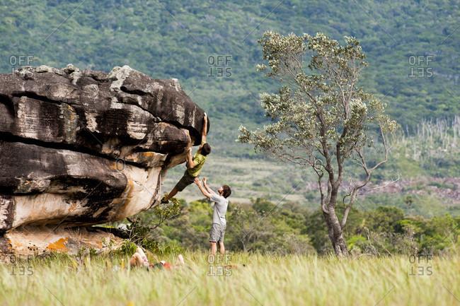 February 5, 2012: Man Helping His Friend While Climbing The Boulder, Bolivar State, Venezuela