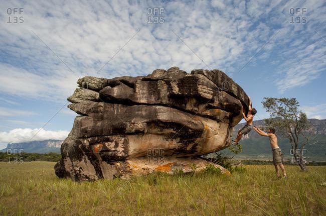 February 5, 2012: Man Assisting His Friend While Climbing The Boulder, Bolivar State, Venezuela