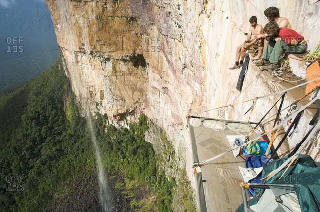 February 5, 2012: Group Of Men Sitting On Edge Of The Rocky Mountain, Bolivar State, Venezuela