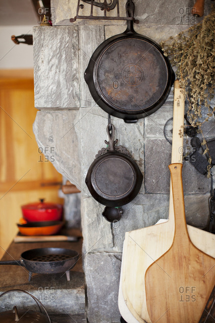 Maine - August 3, 2011: Pans hanging on stone brick wall