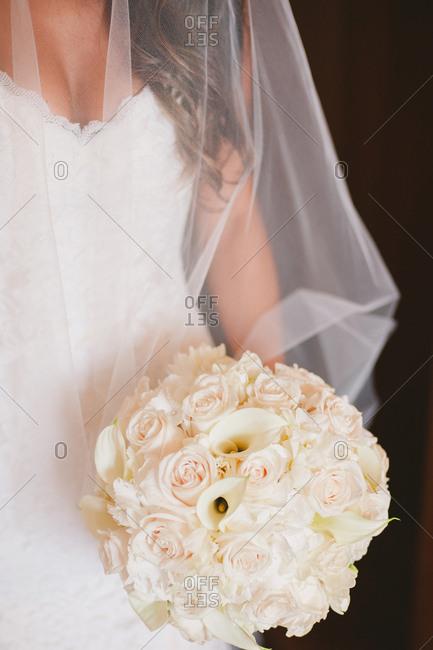 Bride in veil holding rose bouquet