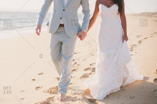 Bride and groom walking beach