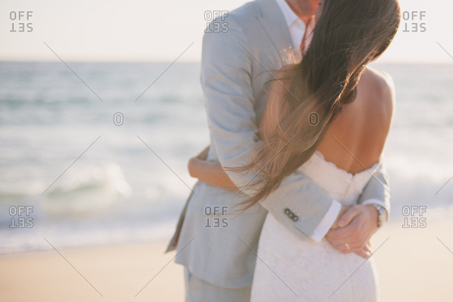 Bride and groom embracing on beach