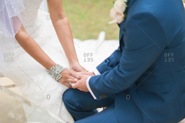 Groom kneeling holding bride's hand