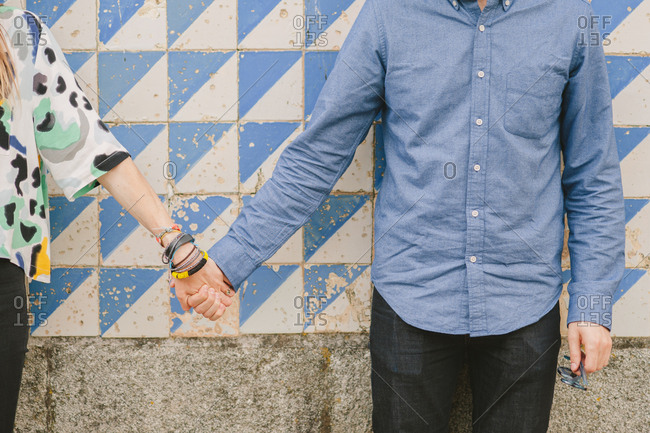 Couple holding hands by tiled wall
