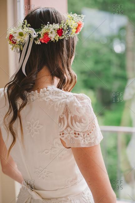 Bride in flower crown by window