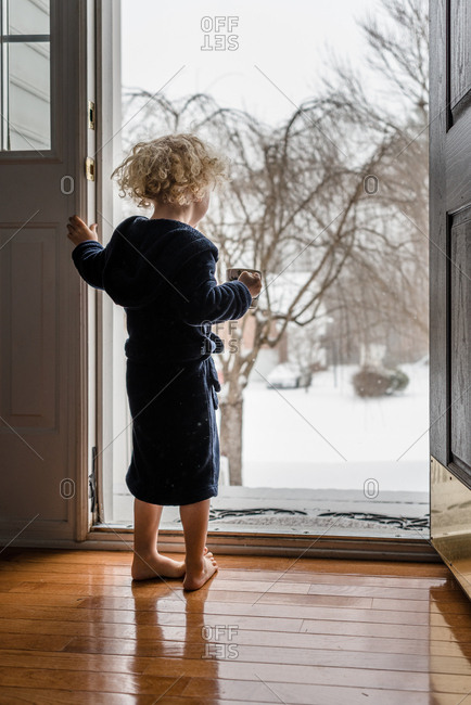 Boy wearing a robe and holding a cup of hot chocolate looking out open door on snowy day