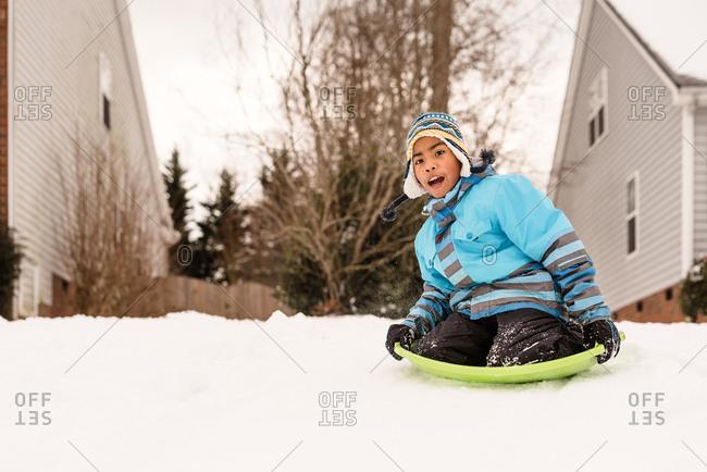 Boy sledding on snow covered yard