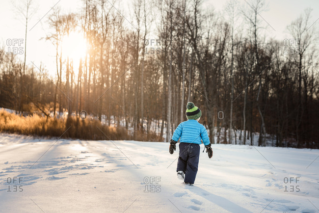 Boy walking on a snow covered meadow